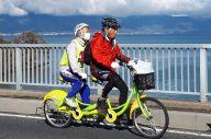 琵琶湖岸をタンデム自転車で走る全盲の山野勝美さん(後ろ)と平岡行雄さん=11月24日午前、滋賀県近江八幡市、大野宏撮影