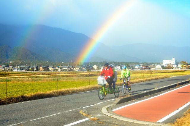 雨も上がり、二重の虹をバックに走る山野勝美さん(後席)と平岡行雄さんのタンデム自転車。段差がある赤い自転車道(右)を避け、車道を走っている。後方は伴走の黒田一臣さん=滋賀県大津市