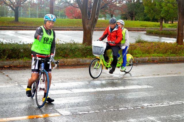奥びわスポーツの森公園を出発し、車道へ出ようとする山野勝美さんと平岡行雄さんのタンデム自転車(右)。伴走の黒田さんが先行し、自動車の通行を警戒している=11月23日午前8時10分、滋賀県長浜市、大野宏撮影
