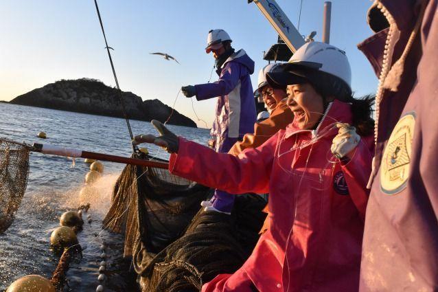 田中優未さんは仲間の漁師に教わりながら、糸で魚を釣り上げた