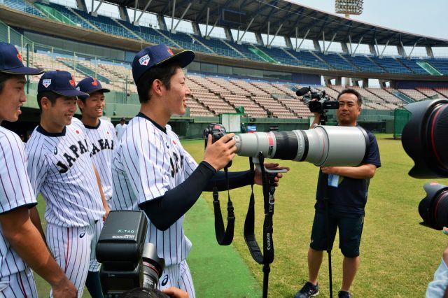カメラマンの機材を借りておどける吉田輝星投手=2018年9月6日