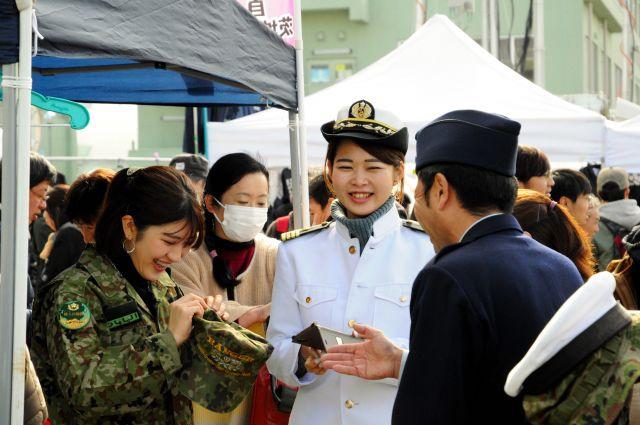 イベントで自衛官の服を着用し、笑顔を浮かべる女性たち=2018年12月2日、茨城県の航空自衛隊百里基地、藤原学思撮影