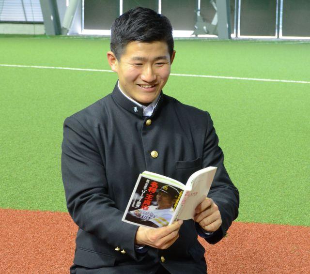 王貞治・ソフトバンク球団会長の本を手にするドラフト3位の野村大樹内野手