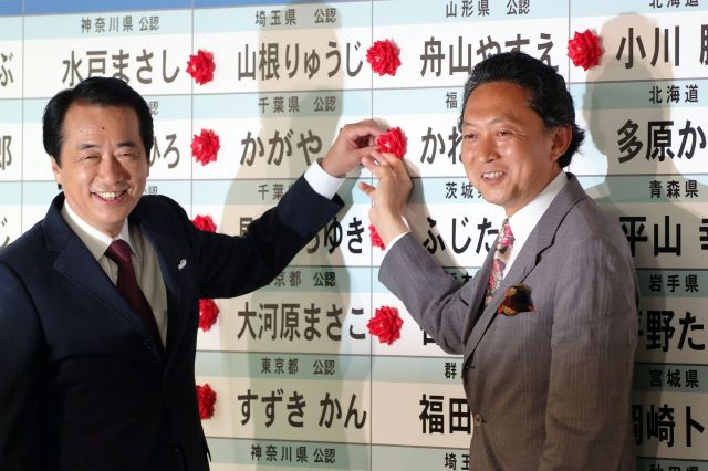 2007年7月の参院選投開票日、民主党本部で当選が確実になった候補者名に赤い花をつける菅直人代表代行(左)と鳩山由紀夫幹事長=東京・永田町
