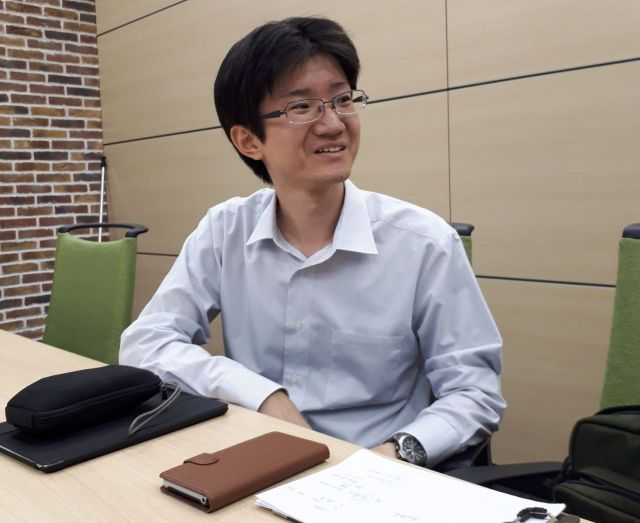 取材中に広報担当者と話す三上雄平さん=滝沢卓撮影