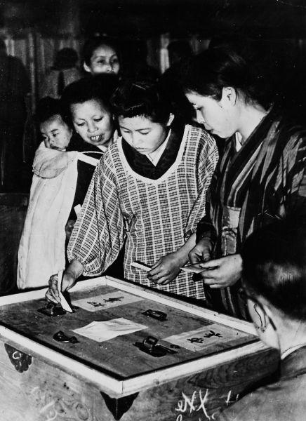 3年ごとの参院選と4年ごとの統一地方選は12年ごとに亥年で重なる。戦後初の1947年の統一地方選で投票する女性ら=大阪市