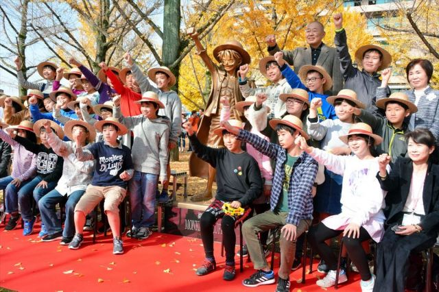 除幕式に参加した益城町の町立広安西小学校の児童らとルフィ像(中央)=2018年11月30日、熊本市