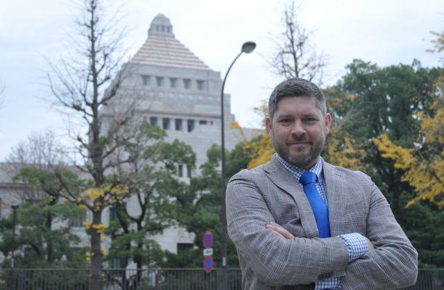 国会議事堂と共に写真に収まるサム・ポトリキオ教授=2018年12月、東京都千代田区、軽部理人撮影