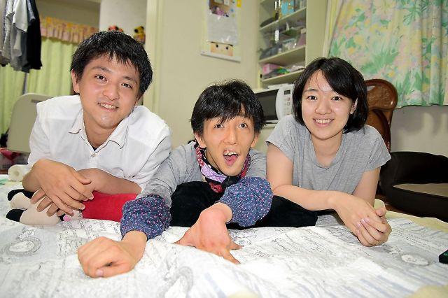 実家の居間でくつろぐ久保田優里さん(右)と兄の植松暖人さん(中央)、弟の洸志さん=大津市