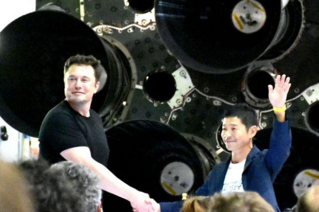2018年9月、スペースX本社に置かれたファルコン9ロケットの前で握手するイーロン・マスクCEOとスタートトゥデイの前沢友作社長=米カリフォルニア州、香取啓介撮影