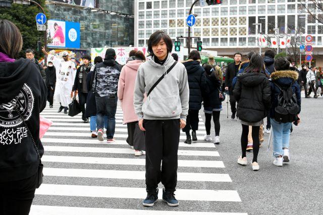 東京・渋谷のスクランブル交差点に立つ若者