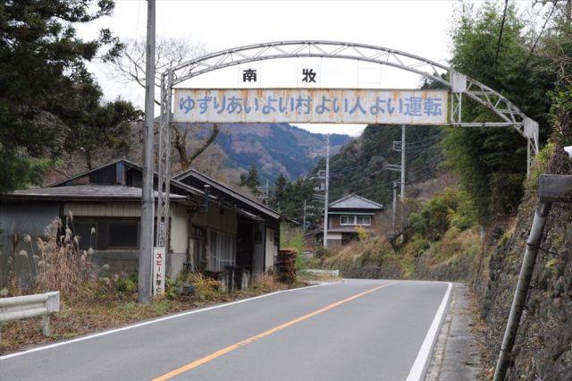 南牧村の県道にかかる看板はさびが目立ち、「村」の文字が抜け落ちたままになっている