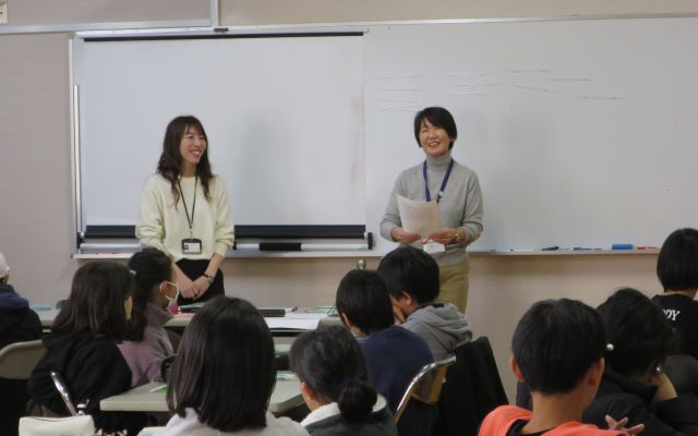 児童を前に話をする山本さん(右)