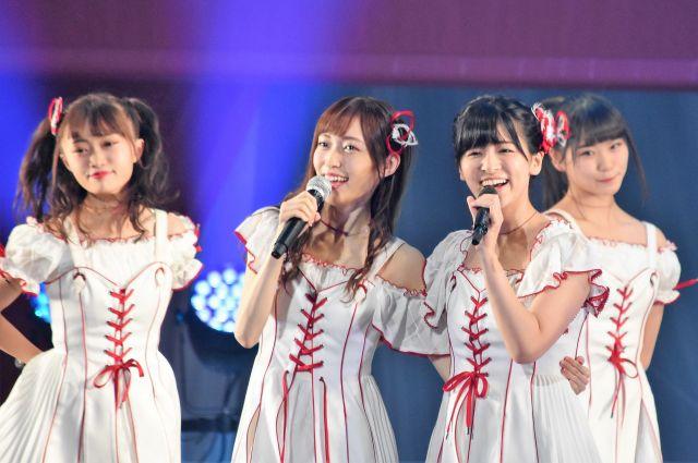事件前のステージ。メンバーと笑顔で歌う山口真帆さん(中央左)=昨年9月、日本武道館