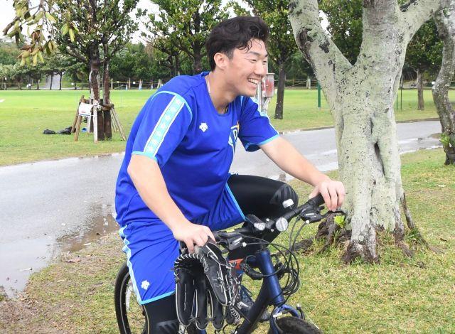 撮影時はスパイクを履いたままだった飯塚悟史投手。「自転車に乗ってるときの写真は恥ずかしいです」