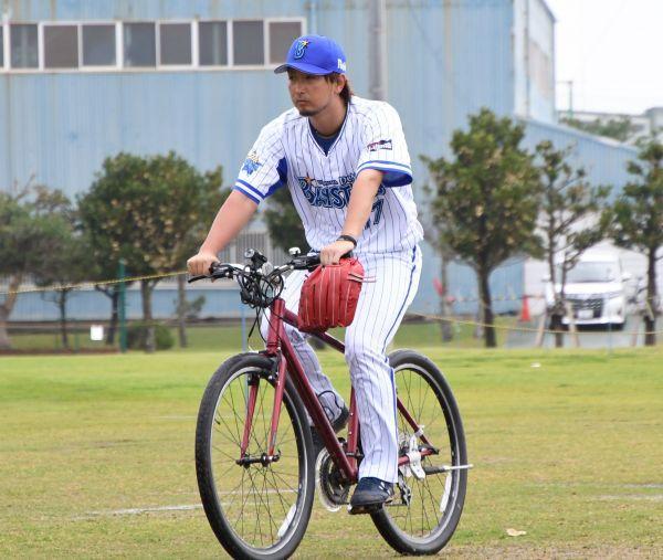 芝生がぬかるんでいる中、自転車で移動する三嶋投手
