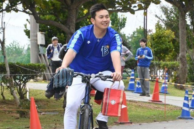自転車に乗ってブルペンを離れる山崎康晃投手