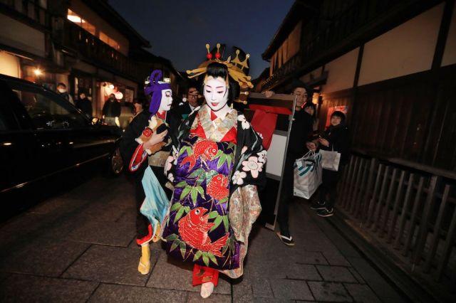 大道具を手に、次の会場となるお茶屋に向かう紗矢佳さん(右)とつる葉さん=2月2日