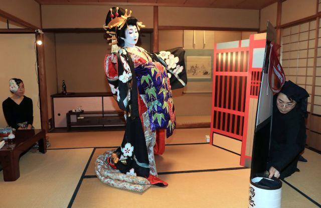 歌舞伎の演目「助六」の揚巻役に分した紗矢佳さん。手作りの舞台背景を黒衣さんが支える=2月2日