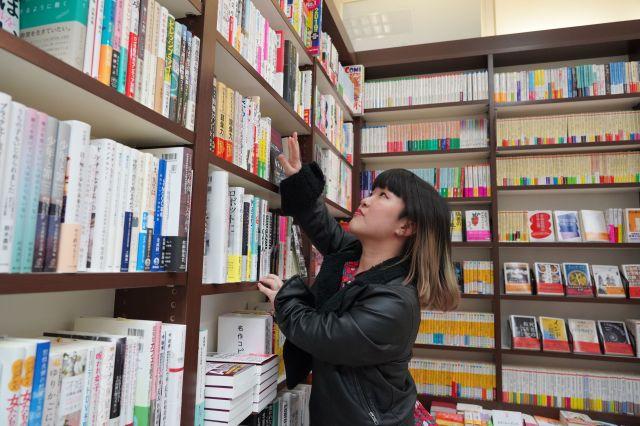 成人の目線ほどの本棚でも、ちびもえこさんは腕を伸ばして本を取ります