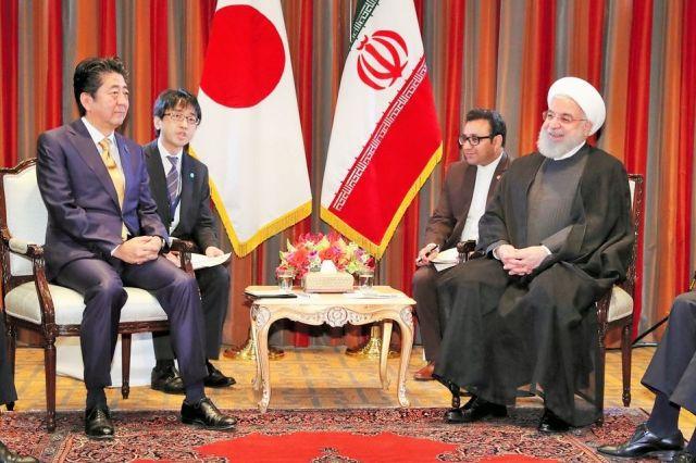 米ニューヨークでイランのロハニ大統領(右)との首脳会談に臨む安倍晋三首相。首相の後ろに座るのが通訳の清水悠史さん=2018年9月26日、岩下毅撮影