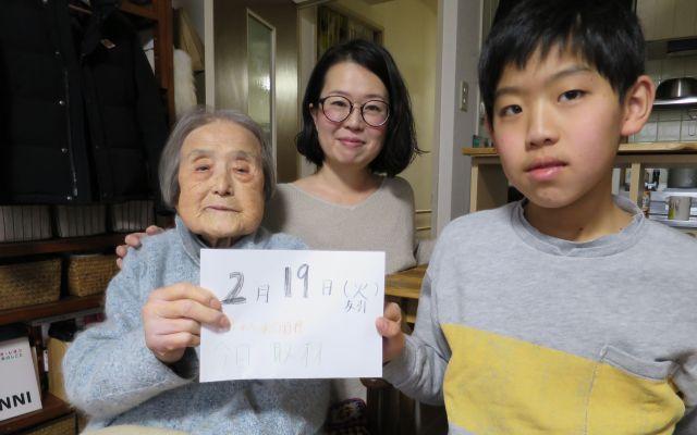取材に訪れた2月19日のカレンダーを持つおばあちゃん(左)。おばあちゃんの目標は「今日、取材」