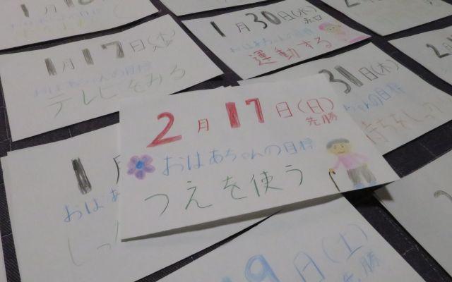 2月17日のカレンダー。おばあちゃんや花のイラストとともに書かれているおばあちゃんの目標は「つえを使う」