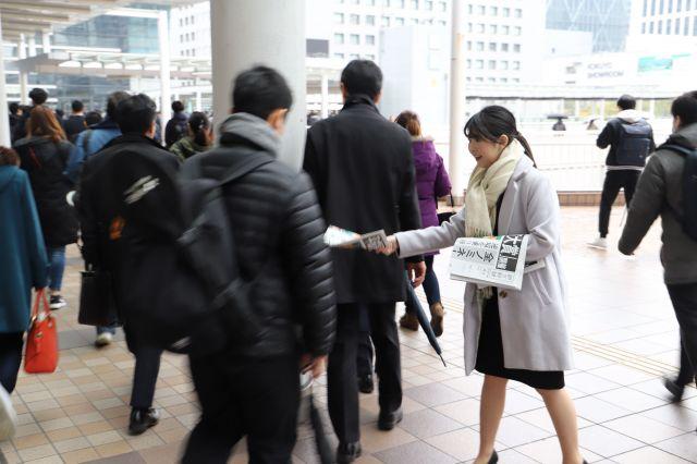 品川駅では、通勤途中の会社員らが広告号外を受け取っていた