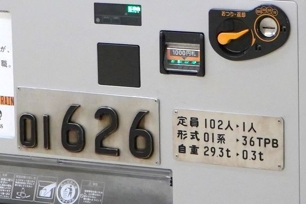 真ん中部分には「01626」という記された車号銘板が。車両の「定員」「形式」「重量」を表す銘板も付いていますが、こちらは実物を加工して設置。車両時代は120人だった定員を、自販機なので1人にするなど細かい点までこだわっています。