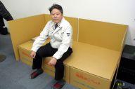 段ボールの簡易ベッドに腰掛ける、Jパックスの水谷嘉浩社長=大阪府八尾市、伊藤弘毅撮影