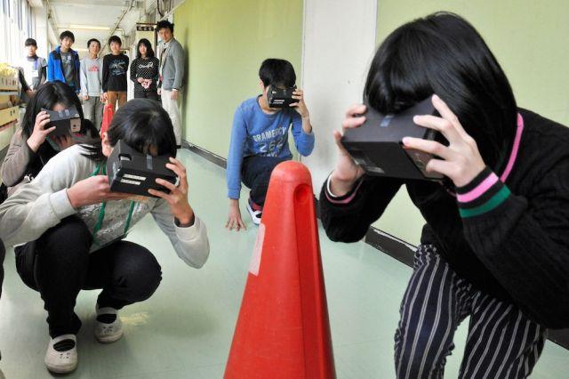 拡張現実(AR)を体験するゴーグルで廊下に充満する煙を疑似体験しながら、姿勢を低くして移動する児童