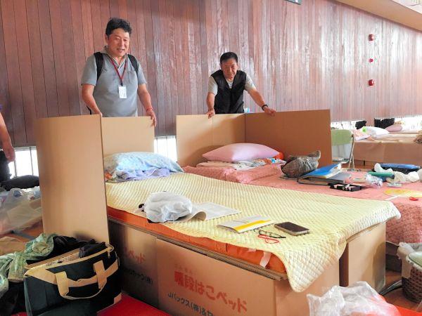 西日本豪雨の被災地で、段ボールベッドに仕切りをつける方法を避難者に教える水谷嘉浩さん(左)=2018年7月、広島市南区の市立楠那小、後藤一也撮影