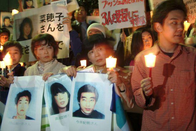 人質となった3人の写真やキャンドルを持ち、救出と自衛隊撤退を訴える人たち。その一方でネット上では「自己責任論」が巻き起こっていた=2004年4月10日、東京・永田町で