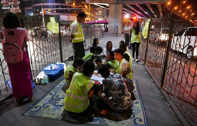 地面にござがしかれ、子どもたちも教師役のボランティアも机を囲んで勉強する=2019年1月、ミャンマー・ヤンゴン