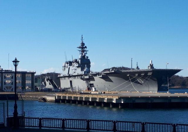 神奈川県の横須賀港に停泊中の護衛艦いずも。左の建物は海上自衛隊横須賀地方総監部=3月13日