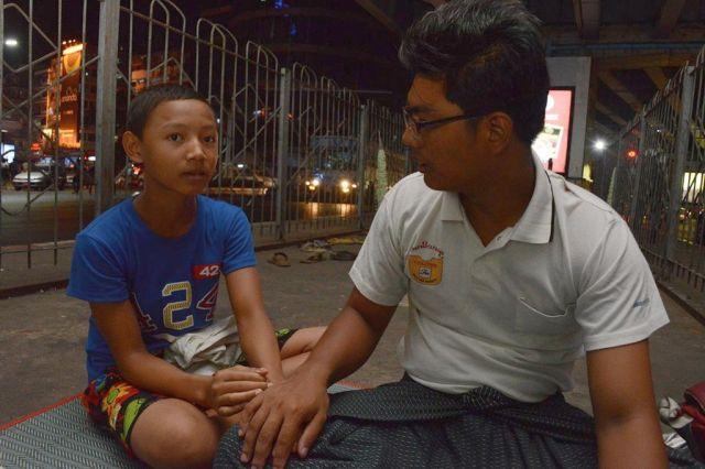 子どもと話す、テットアウンリンさん(右)。勉強だけでなく、生活の相談にも乗っているという=2018年9月、ミャンマー・ヤンゴン