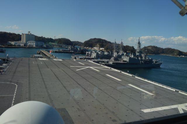 護衛艦いずもの航空管制室から艦尾方向の甲板を望む。右奥には海自のふつうの護衛艦が並ぶ=3月13日、横須賀港
