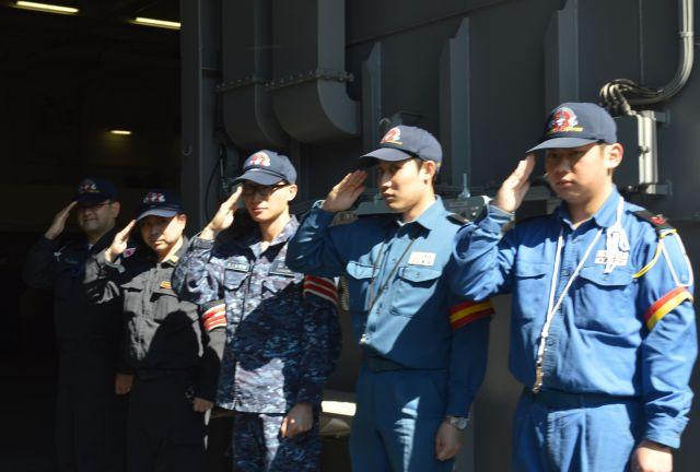取材に訪れた報道陣に敬礼する護衛艦いずもの乗員ら=3月13日、横須賀港