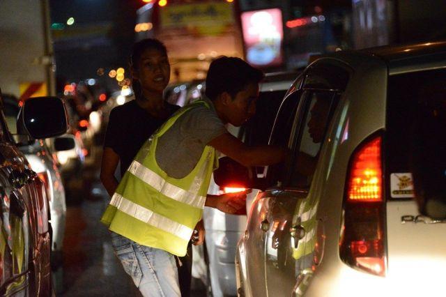ボランティアの若者たちは、子どもたちが売れなかった花を停車した車の運転手らに売る=2018年9月、ミャンマー・ヤンゴン