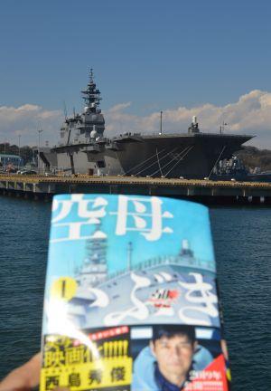 護衛艦いずも(奥)と、漫画「空母いぶき」(小学館)の単行本=3月13日、横須賀港