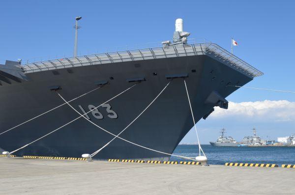 長さ248m、幅38mのいずもの艦首。地元の人が「今日は183が来てる」と艦番号で話していた。右には米海軍横須賀基地の船が並ぶ=3月13日、横須賀港。以下同じ