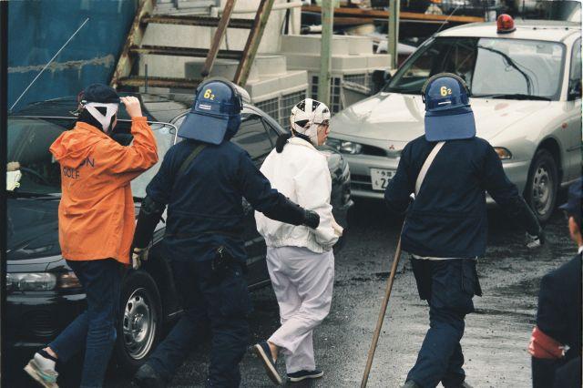 オウム真理教第6サテイアンの建物から連れ出されるオウム真理教の信徒たち=1995年5月16日