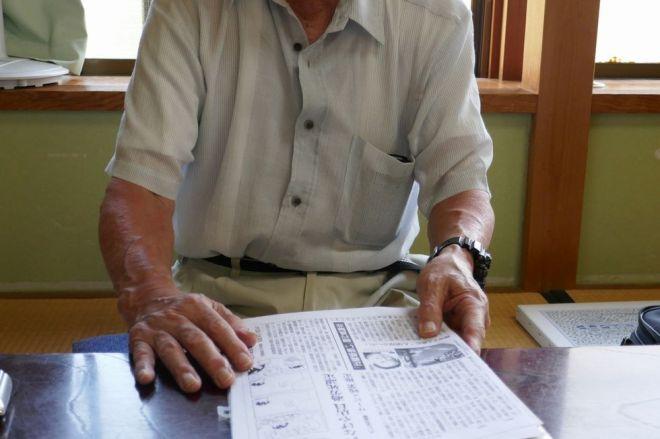 過労死した男性の父親。労災認定を伝える新聞を手元に置き、会社の責任を訴えた