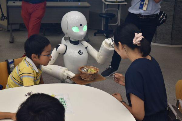 遠隔操作で、子どもたちにチョコを手渡すOriHime-D