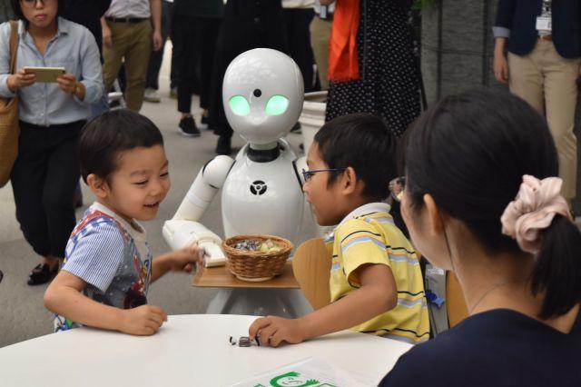 「分身ロボットカフェ」ではOriHime-Dが遠隔操作で子どもたちにチョコを渡した=2018年8月22日、東京都港区の日本財団ビル