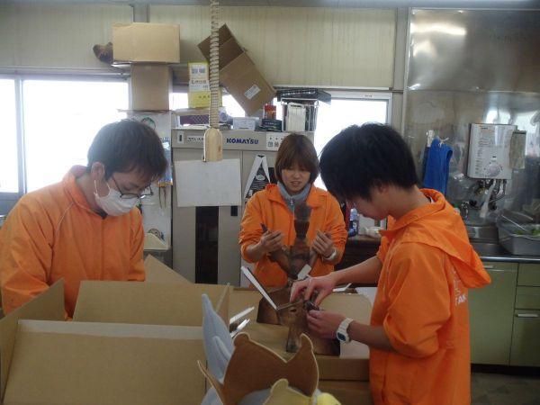 「カピバラの落とし物」の箱を組み立てて中身を詰める水族館職員たち