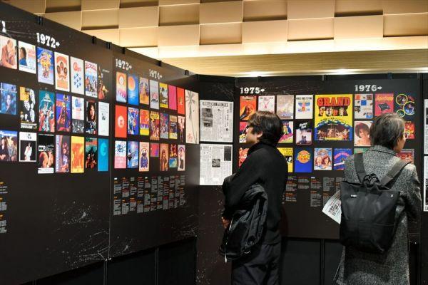 1970年代の来日公演ポスターに、内覧会で見入る人たち=2019年3月7日、東京・有楽町