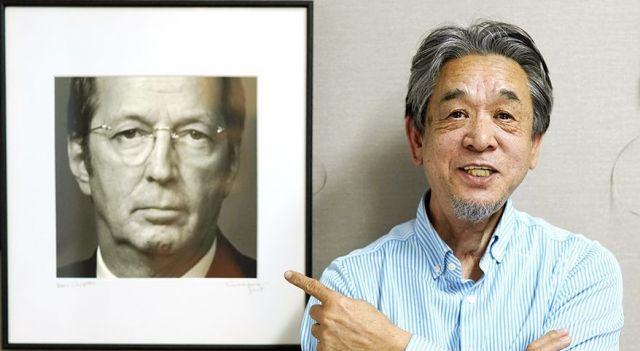 ウド―音楽事務所の高橋辰雄さん。左はギタリスト、エリック・クラプトンの肖像写真=鬼室黎撮影