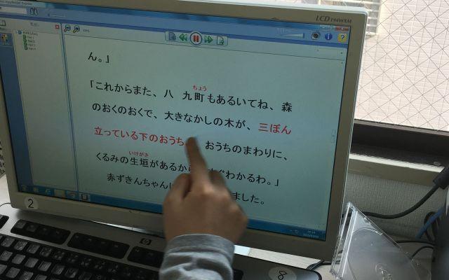 聴覚優位の子どもは、本の文章をパソコンで追いながら、ヘッドフォンから聞こえてくる音声で理解していく=東京都文京区の「未来教室」