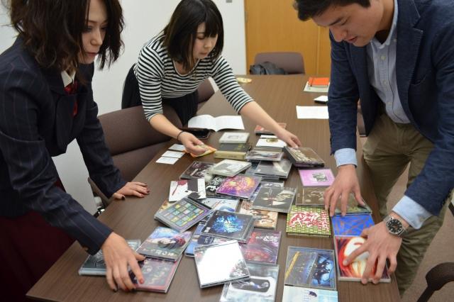 「参考用に」と藤谷さんが用意してくれた、大量のV系バンドCDを並べる参加者たち=野口みな子撮影